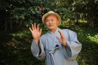 Mnich Wonjeong ukazuje háj z kamélií za klášterem Sonunsa