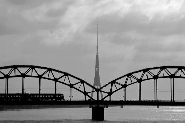 Jernbanebro over elven Daugava i Riga, Latvia, med det ikoniske radiotårnet sentrert for god symmetrisk effekt.