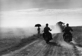 Copyright: Dei motociclisti e una donna percorrono la strada da Nam Dinh a Thai Binh, Indocina (Vietnam), maggio 1954 - © Robert Capa © International Center of Photography / Magnum Photos