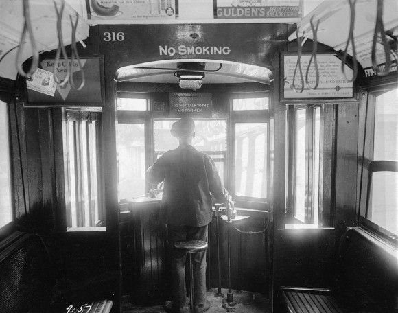 A motorman operates a trolley cars near Williamsburg Bridge, on September 25, 1924. Signs advertise almonds, cold remedies, mustard, and stove polish. (Eugene de Salignac-Courtesy NYC Municipal Archives)