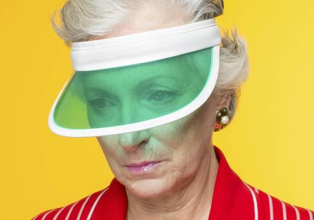 Frau mit grüner Schildkappe vor gelbem Hintergrund