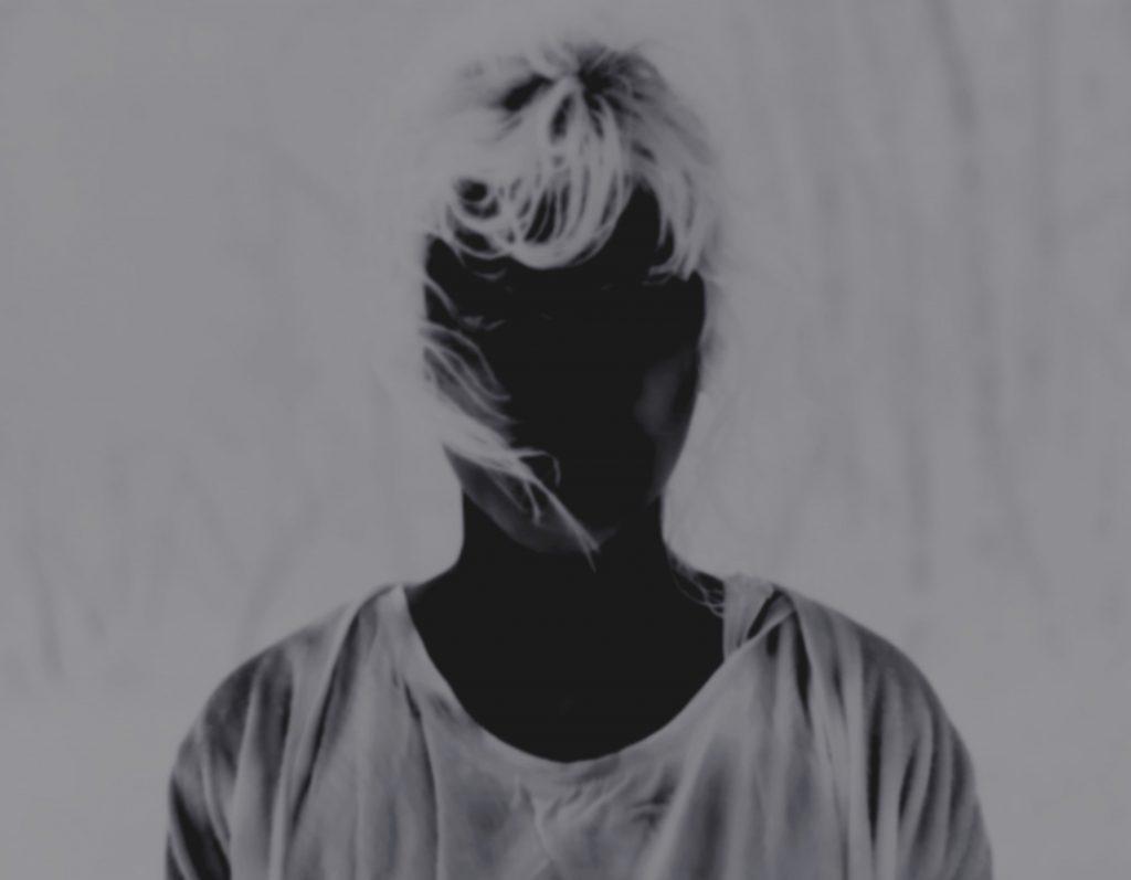 Person mit verdunkeltem Gesicht und hellen Haaren