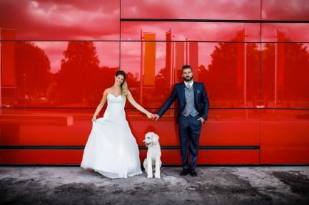 Hochzeitsfotos vor roter Wand mit Hund. Besitzer der Fahrschule fahrszination.