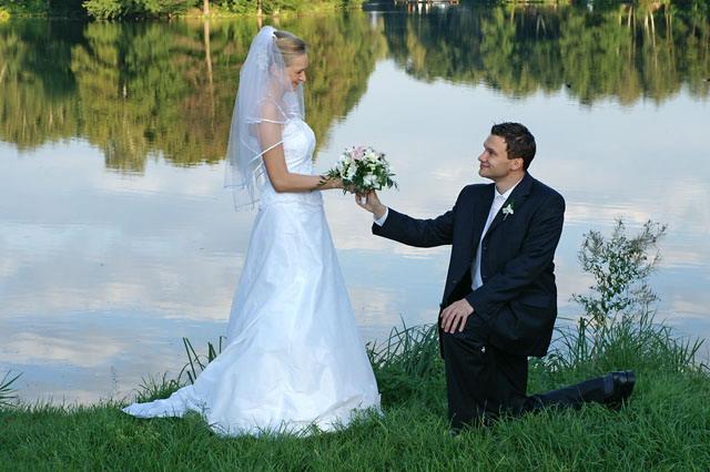 Klęczący pan młody daje kwiaty swojej żonie