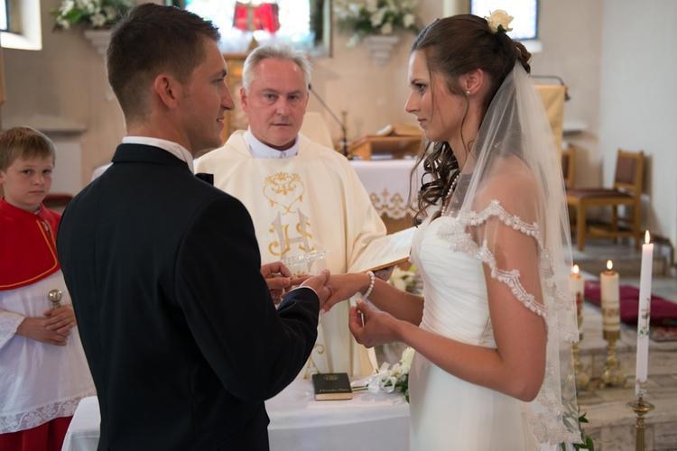 Po przysiędze małżeńskiej para młoda zakłada obrączki