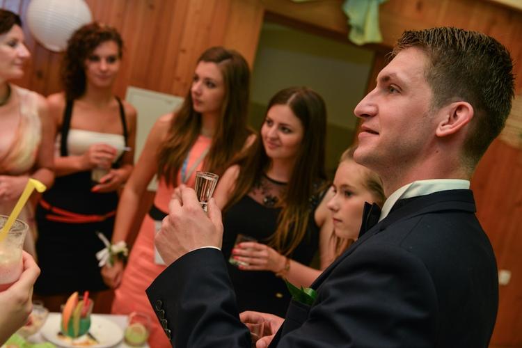 Pan młody wznosi toast wraz z weselnym goścmi