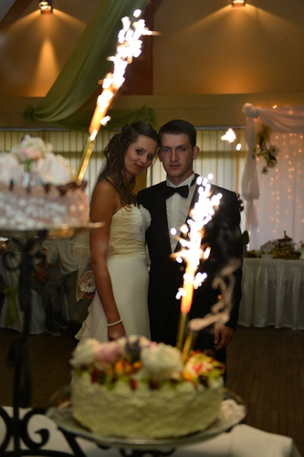 Tort ślubny i para młoda w tle