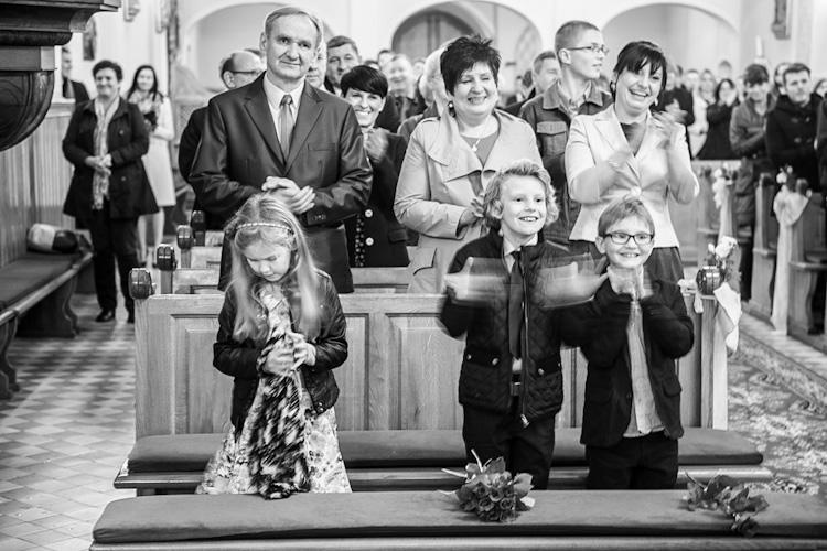 Rodzice pary młodej i dzieci radośnie wiwatujące w kościele podczas ślubu