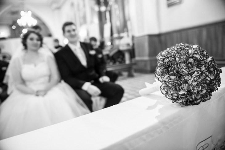 Para młoda podczas ślubu w kościele. Bukiet na pierwszym planie