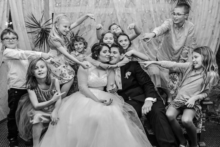 Fotografia ślubna. Para młoda wotoczeniu dzieci naswoim weselu