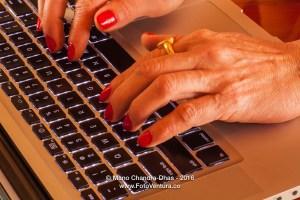 Older Latin lady's hands on laptop computer keyboard
