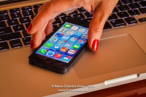 Latin lady's fingers picking up iPhone5 from computer keyboard;