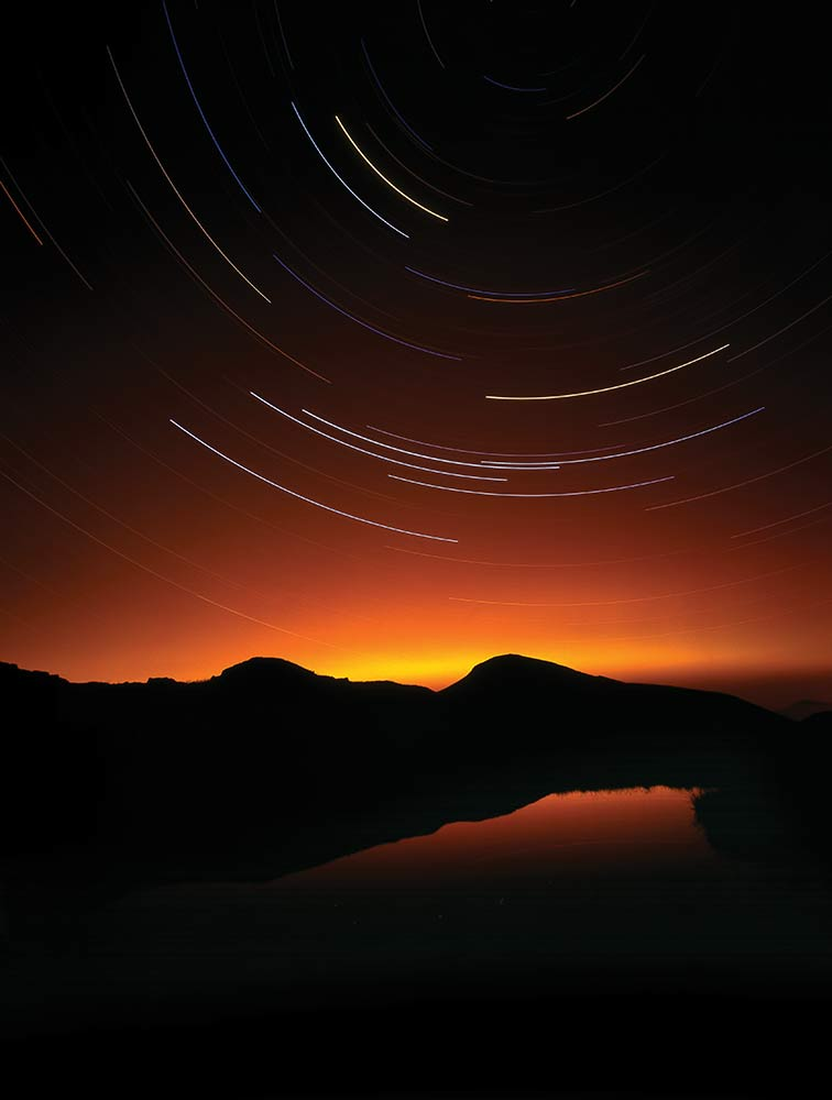 A 2 hour exposure looking north from below Scafell Pike in the Lake District. At the centre of the rotation is Polaris, the North Star. The yellow and orange glow is light pollution from Carlisle and was barely evident to the eye, the long exposure has emphasised it. Mamiya 7II medium format camera using Fuji Velvia 50ASA film, tripod. © Stuart Holmes 2014