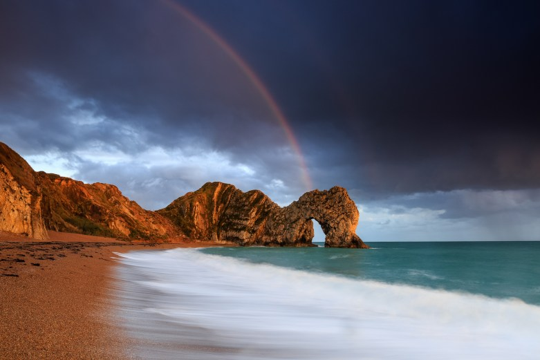 The 'classic' view of Durdle Door from the beach, with the warm glow of the evening sun and a rainbow to set it off. Canon 5D III, 16-35mm f/2.8 at 21mm, ISO 125, 2.5 seconds at f/11. © Mark Bauer