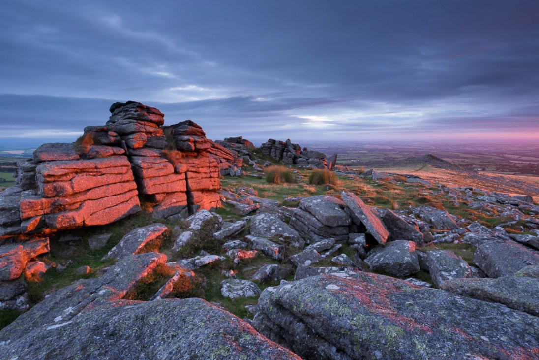 First light at sunrise glows against Belstone Tor, Dartmoor National Park, Devon, England. Summer (August) 2015. © Adam Burton