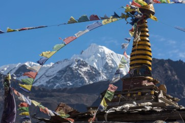 Prayer flags flutter on top of a stupa with snowy peaks above. Canon 5D MkIII, 70-300mm at 182mm, ISO 100, 1/320 sec at f/9. © Stuart Holmes.