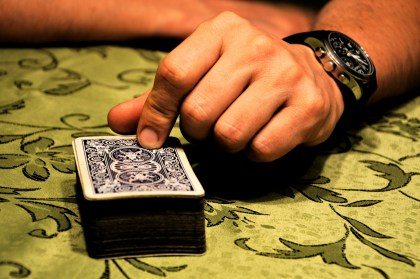 Photo of man's hand resting on a deck of cards