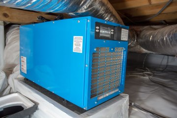 Low profile dehumidifier system in crawl space of a home