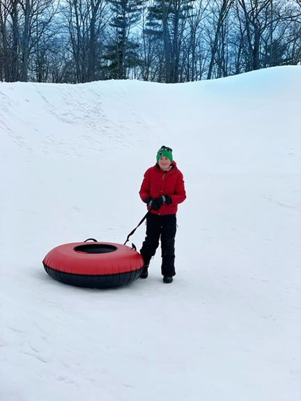 boy with red coate and green hat and snow tube