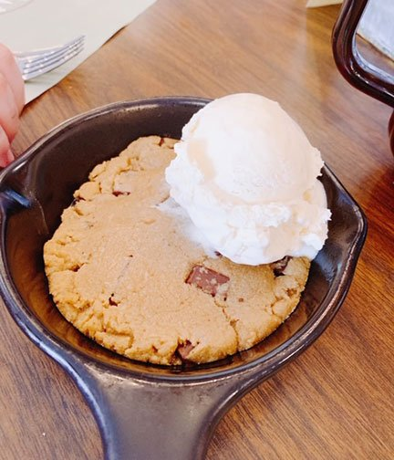 warm chocolate chip cookie in a skillet with a scoop of vanilla ice cream