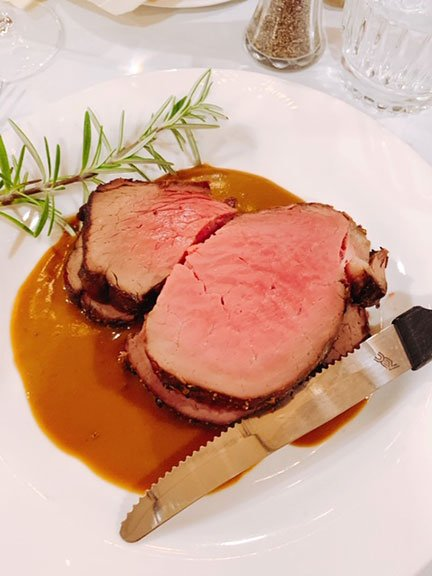 prime rib on a plate with rosemary and steak knife