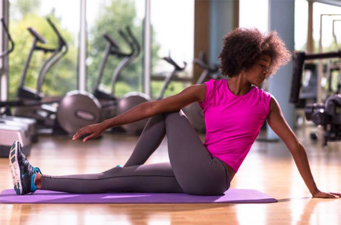 stretching woman on pnk top seated on mat hip stretch