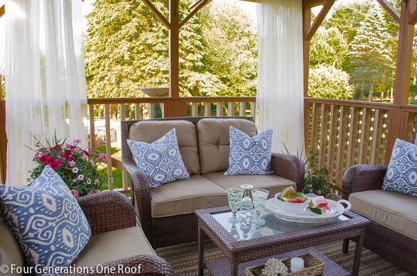 deck with outdoor curtain rod and outdoor white grommet style curtains, brown wicker outdoor furniture, blue throw pillows, watermelon