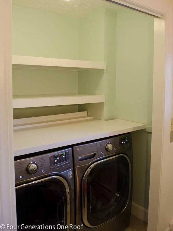 green laundry closet, white wood floating shelves, side by side washer dryer
