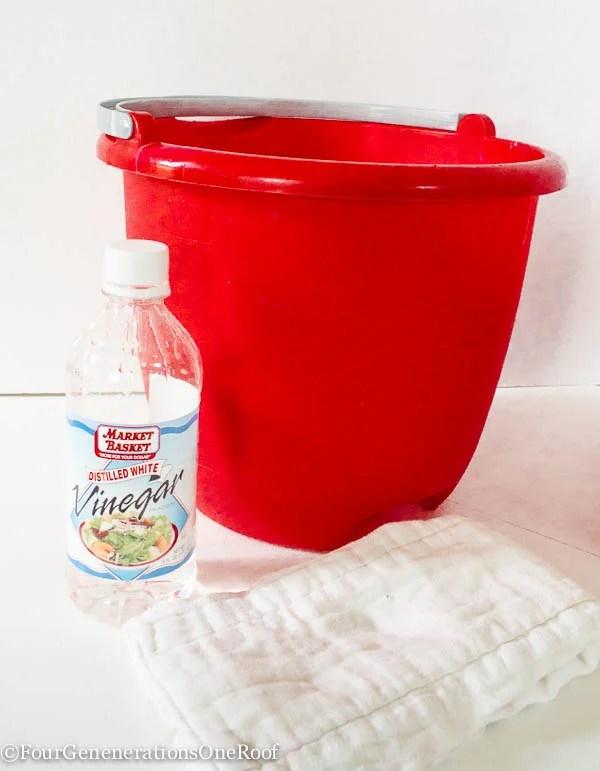 red bucket, bottle of vinegar, diaper cloth,