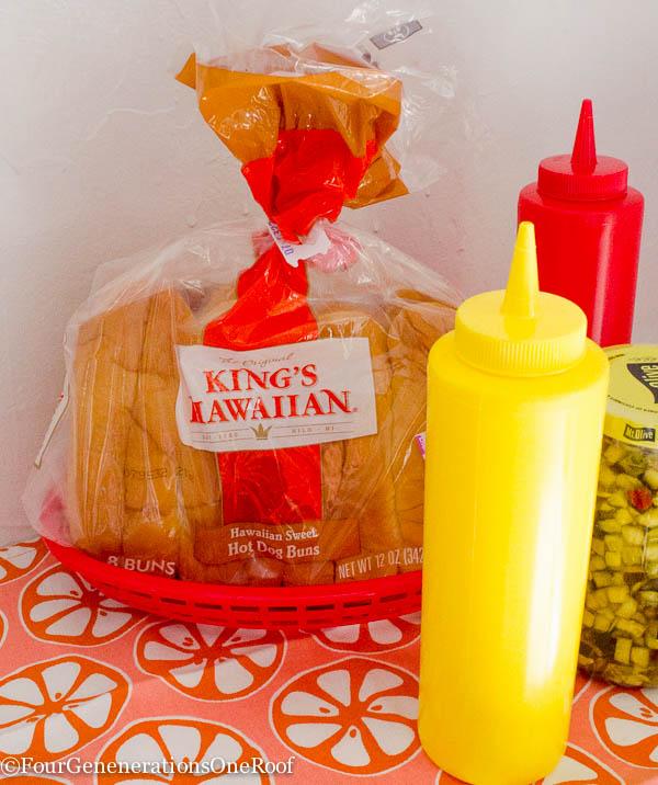 Kings Hawaiian hot dog rolls in red basket, mustard, ketchup and relish on summer tablecloth