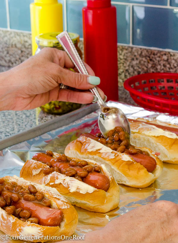 Kings Hawaiian hot dog rolls with butter spread on top, baked beans, cookie sheet lined with tin foil, relish, ketchup