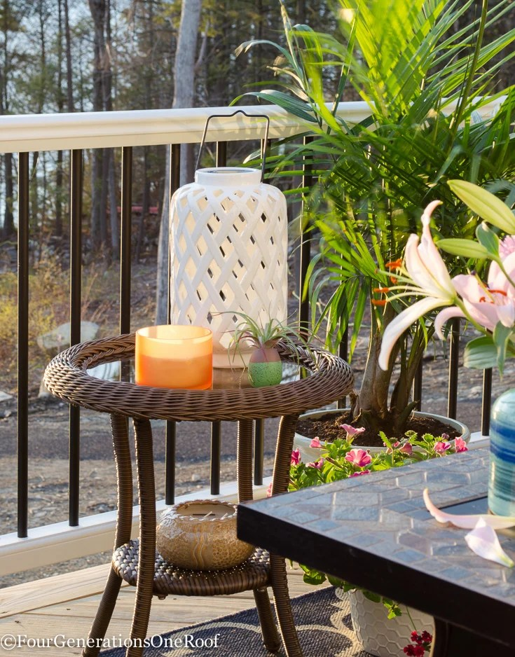 white outdoor lantern, wicker side table, firepit, indoor plant