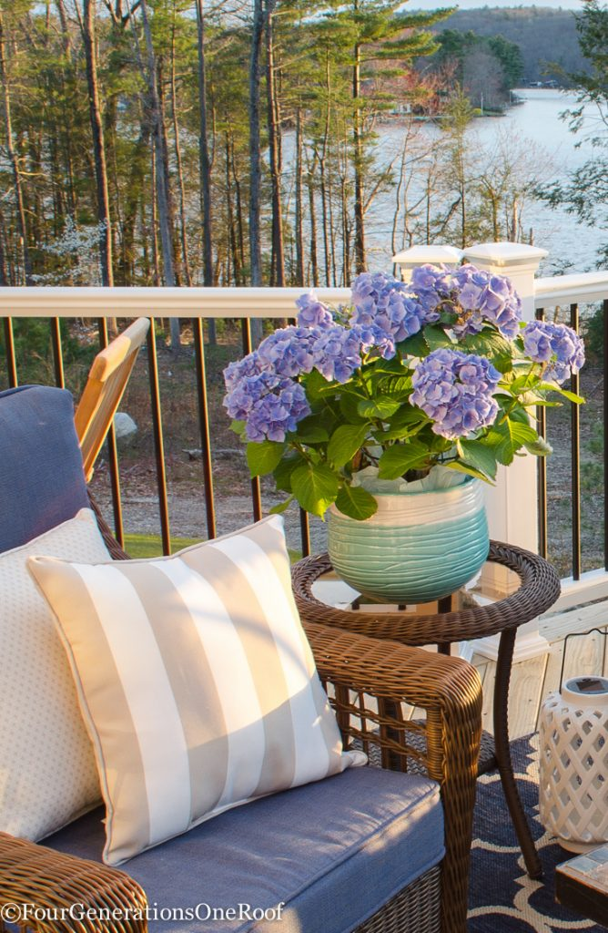 firepit, tan striped outdoor pillow, hydrangea, coral pillow, blue rattan outdoor wicker set, green blue vase, white vase, indoor plant