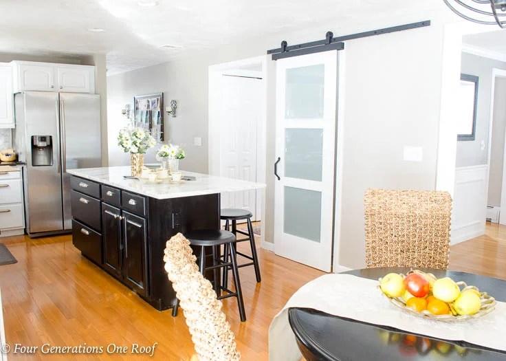 White kitchen, black island, sisal chairs, modern barn door black sliding door hardware, Barn Door Installation without Removing Door Trim