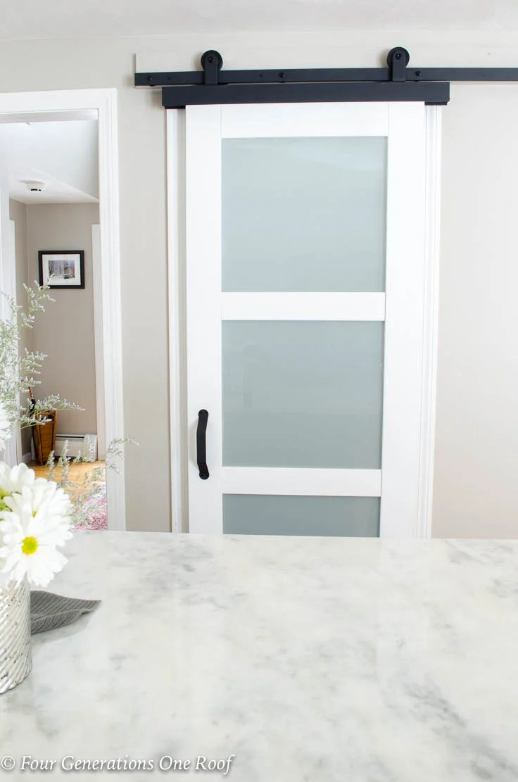 Jeldwen white modern barn door, black sliding door hardware, white quartz countertopBarn Door Installation without Removing Door Trim