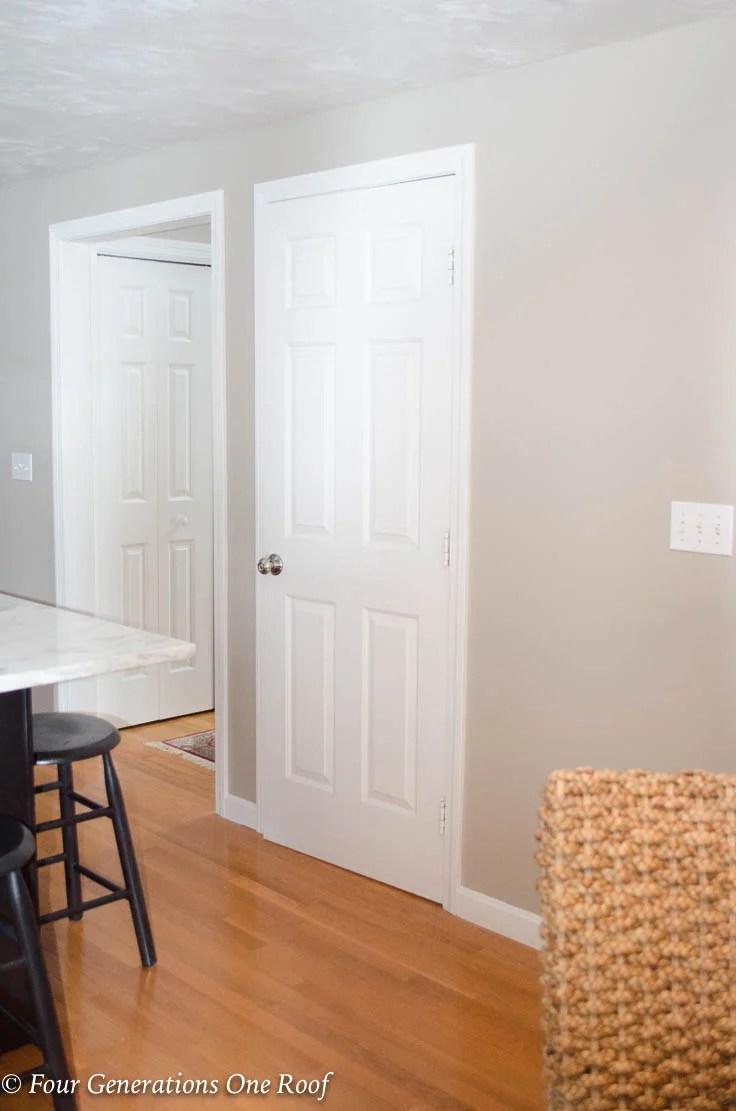 White kitchen basement door, sisal chair, Barn Door Installation without Removing Door Trim
