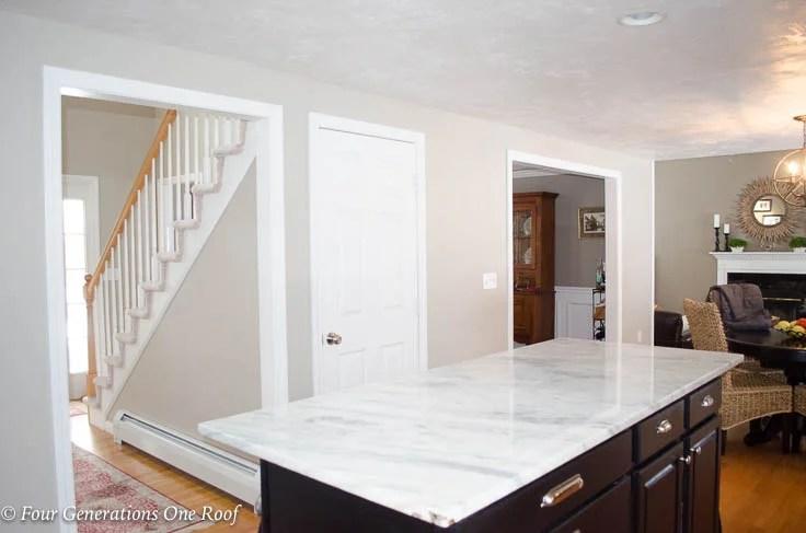 White basement kitchen door Barn Door, white quartz countertop, black island, Installation without Removing Door Trim