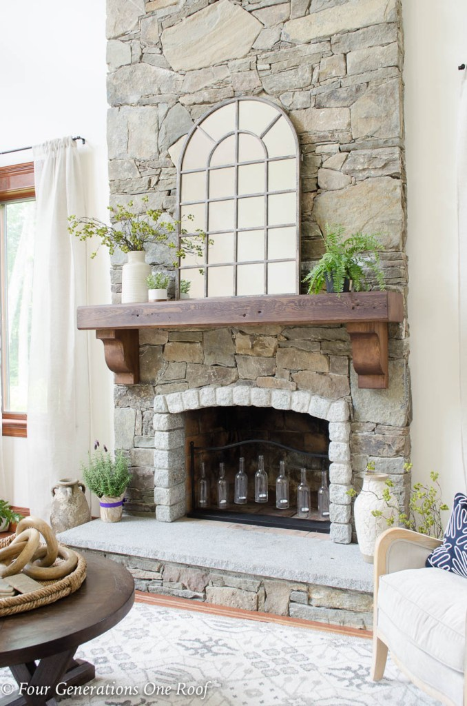 Stone fireplace, dark brown wood mantel, large mirror, greenery in vases on mantel, candles in fireplace, linen curtains