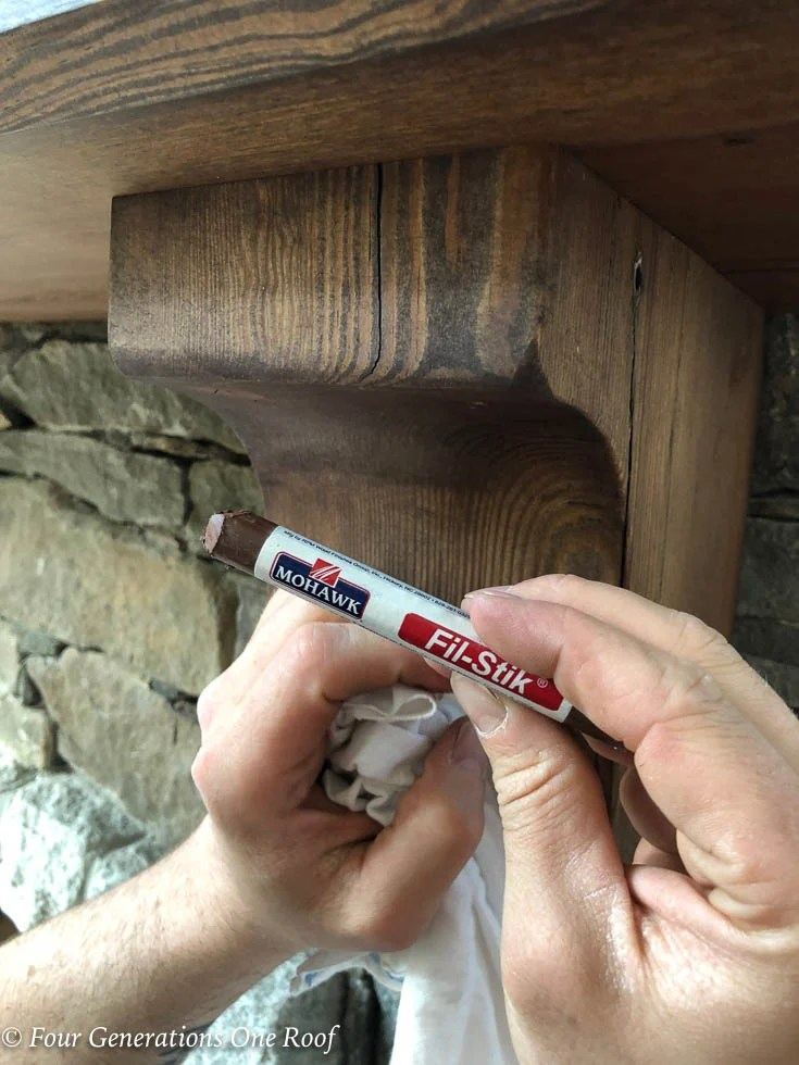 100 year old southern yellow pine beam mantel and corbels being screwed to mantel, stone fireplace, fill stik crayon by Mohawk