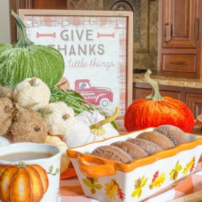 Kitchen Island Fall Snack Station with orange plaid tablecloth, Harvest dog sign, Harvest bakeware, pumpkins, apple pie, apple cider, donuts and baked goods