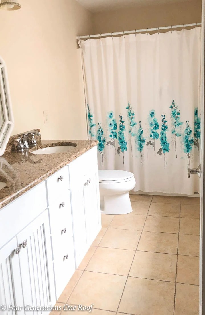 Narrow bathroom with old white toilet, brown tiled floor and brown walls