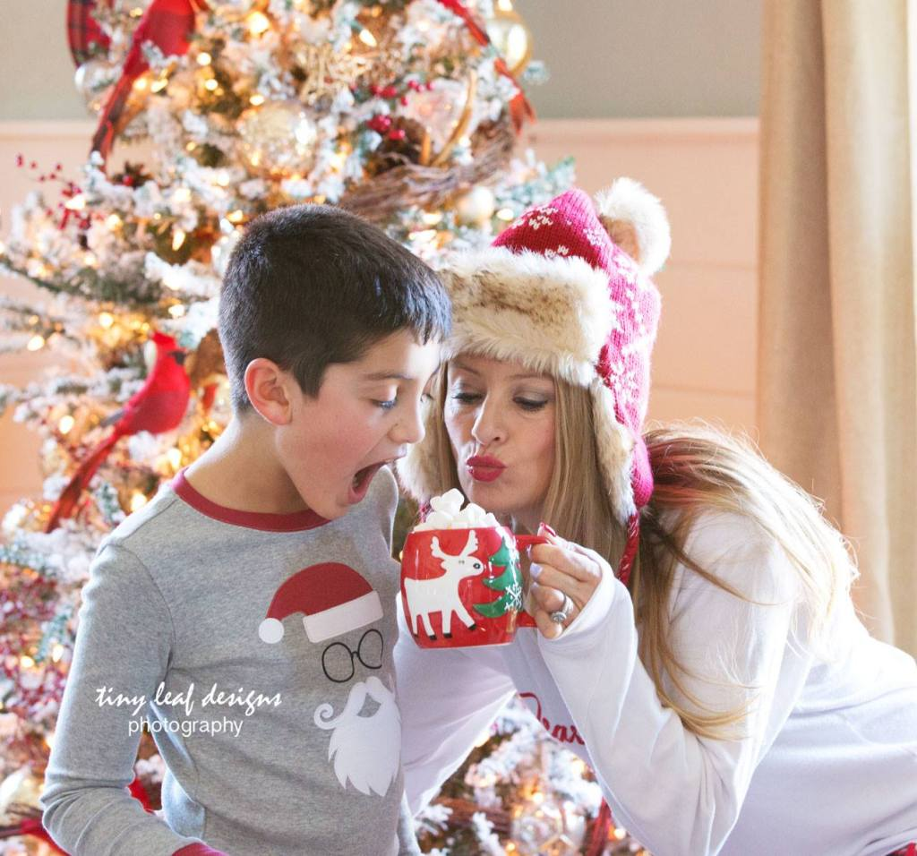 mom and son red and white christmas tree and hot chocolate