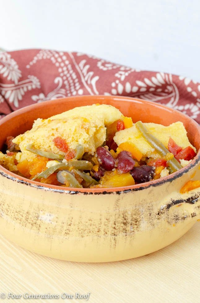 Yellow crock dish with beef stew + vegetables + cornmeal dumplings, red patterned napkin