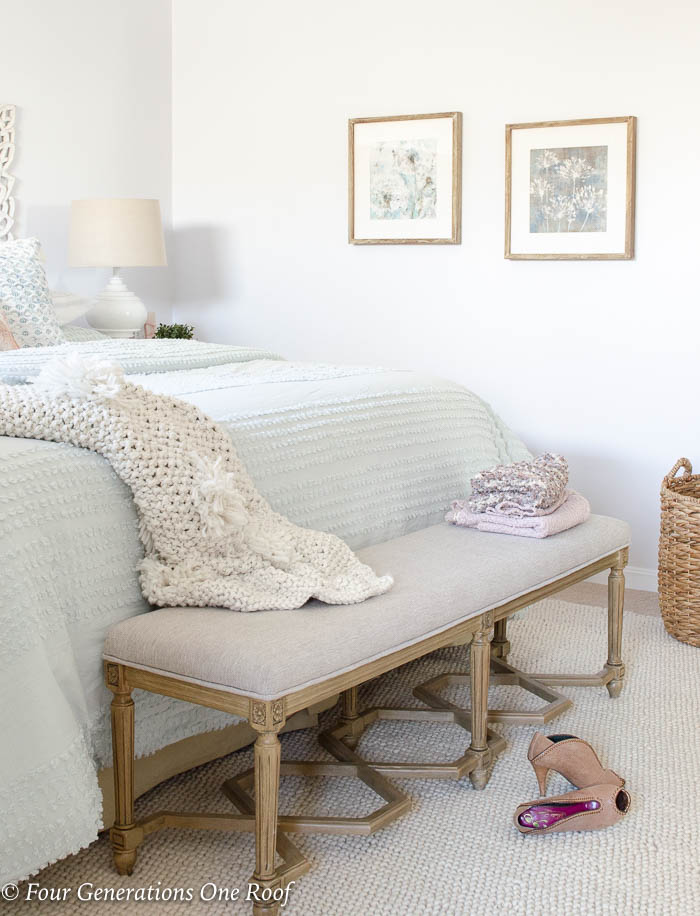 white scroll headboard, mint green bedding, mint green comforter, white night table, white lamp, blue tassel throw pillow, green plant, french country bench, cable knit beige throw blanket