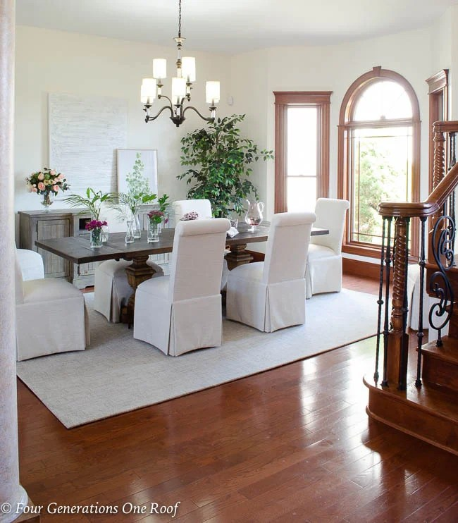 Arhaus dining table, slipcovered parson chairs, Hinkley Modern Traditional Chandelier lighting updates, greenery, Dash and Albert off white wool rug