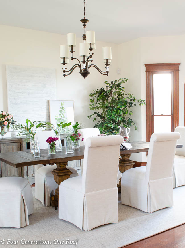 Arhaus dining table, slipcovered parson chairs, lighting updates with Hinkley Modern Traditional Chandelier, greenery, Dash and Albert off white wool rug