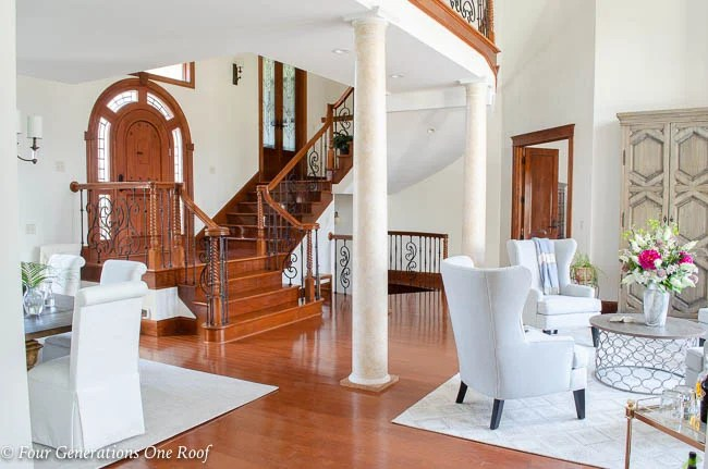large foyer entrance with stained stairs,arched wood door, italian columns, black iron balusters, wing back chairs