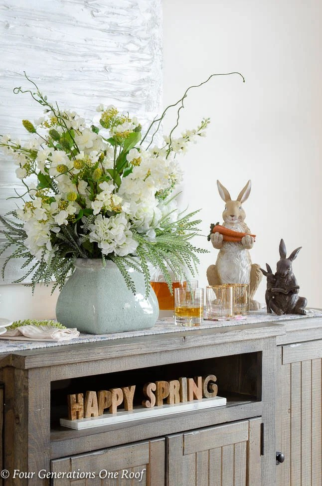 Wood farmhouse buffet table, wood Easter bunnies, flowers, white modern artwork, white Tuscan dishes, Happy Spring Sign,