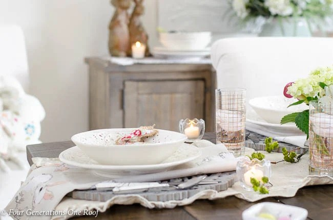 White slipcovered dining room chairs, wood farmhouse table, stained trim, white tuscan dishes, Easter linens, hydrangeas, wood scroll chargers, gold glassware, Easter bunnies, ruffled beige table runner