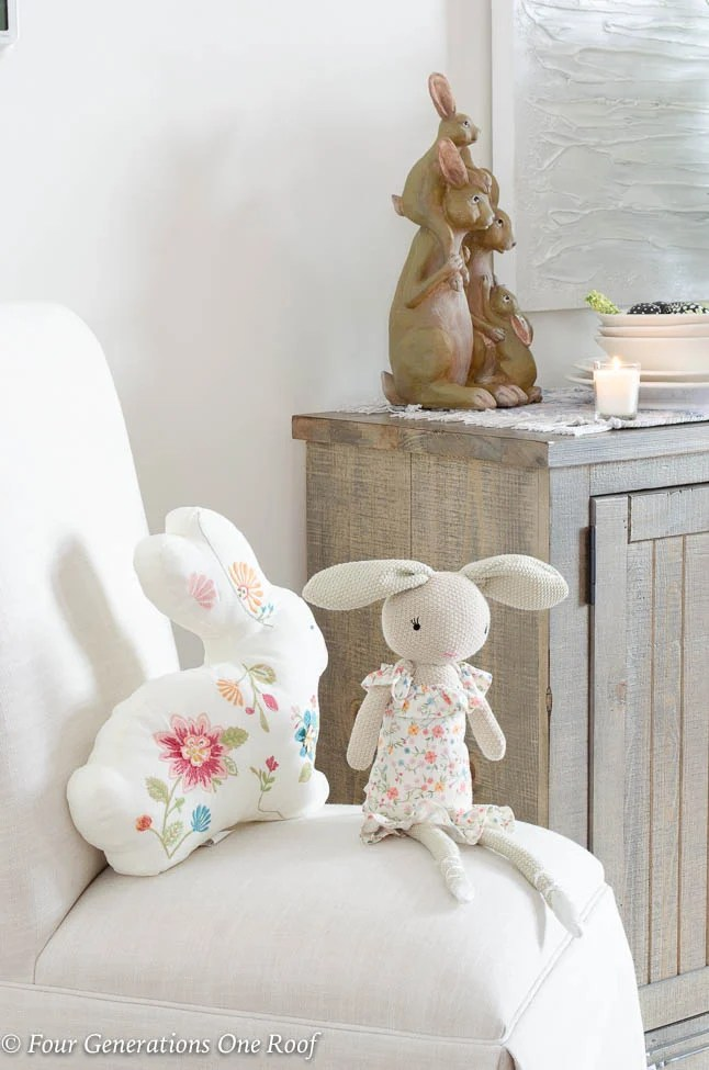 white slipcovered parson chair with decorative bunny stuffed animals, wood buffet table, wood bunny Easter decorations